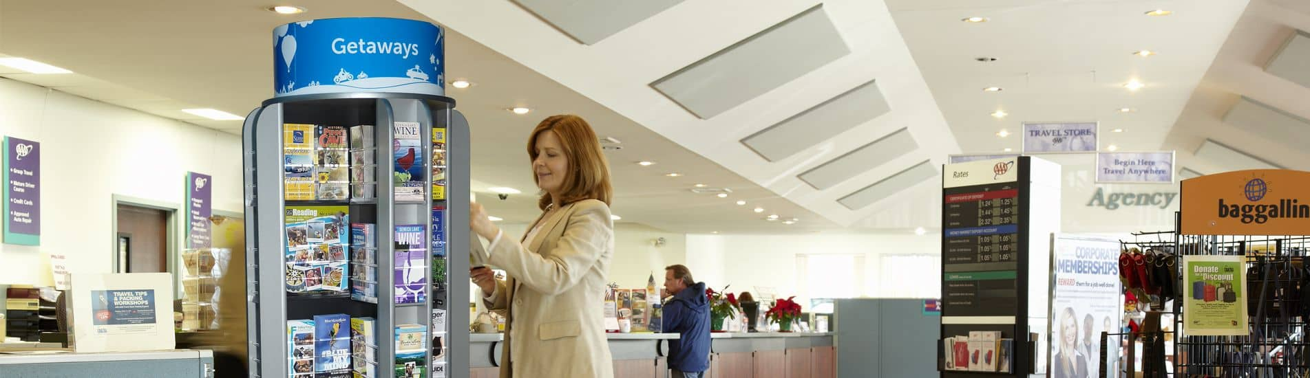 woman selecting literature from a rotating display in a travel agency lobby