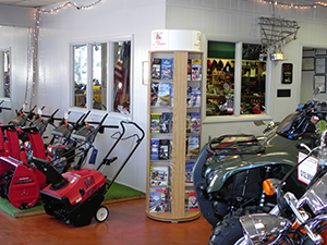 a large rotating literature display in the corner of a business next to snow blowers