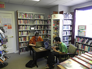 a large rotating display in a library behind two students studying at a desk