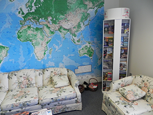 a rotating literature display rack in the corner of an office next to a large wall map