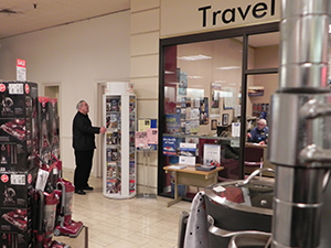 an older gentleman looking at a large rotating literature display outside a travel agency