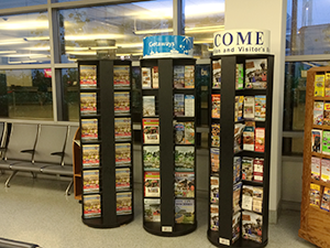 3 large rotating literature displays next to each other in an airport