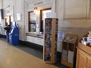 a large rotating literature display next to a ticket booth and a small magazine bin